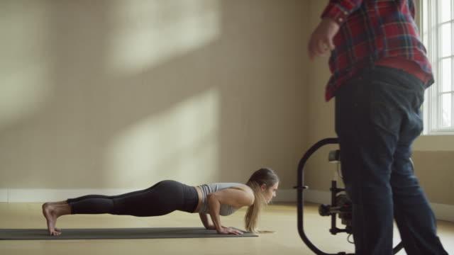 Medium slow motion shot of photographer recording woman performing yoga / Provo, Utah, United States