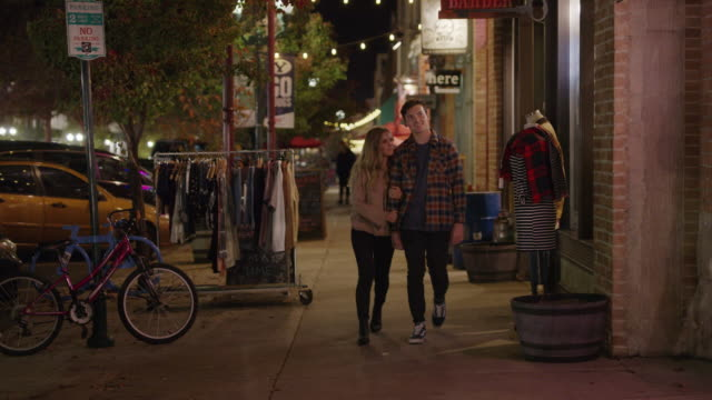 stockvideo's en b-roll-footage met medium slow motion shot of romantic couple walking in city at night / provo, utah, united states - provo