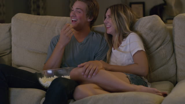 Medium slow motion shot of teenage couple watching television / Cedar Hills, Utah, United States