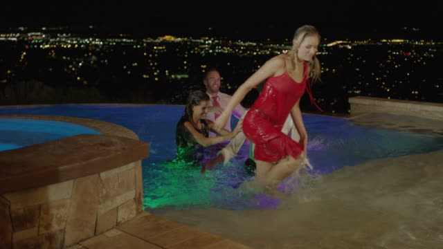 medium slow motion shot of well-dressed people exiting pool / cedar hills, utah, united states - spingere video stock e b–roll