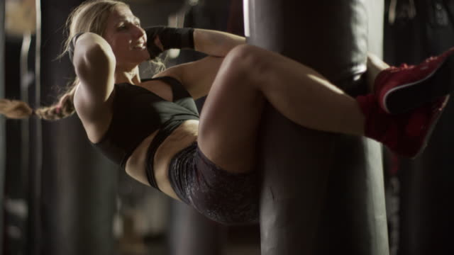 Medium slow motion shot of woman doing extreme sit-ups on heavy bag / Lehi, Utah, United States