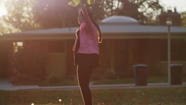 medium slow motion shot of woman doing jumping jacks on lawn / orem, utah, united states - orem bildbanksvideor och videomaterial från bakom kulisserna