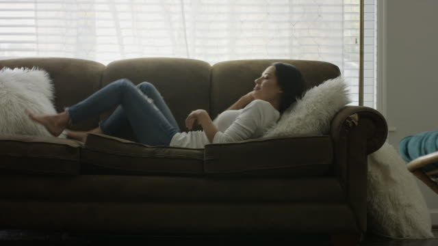 Medium slow motion shot of woman falling onto sofa and napping / Provo, Utah, United States