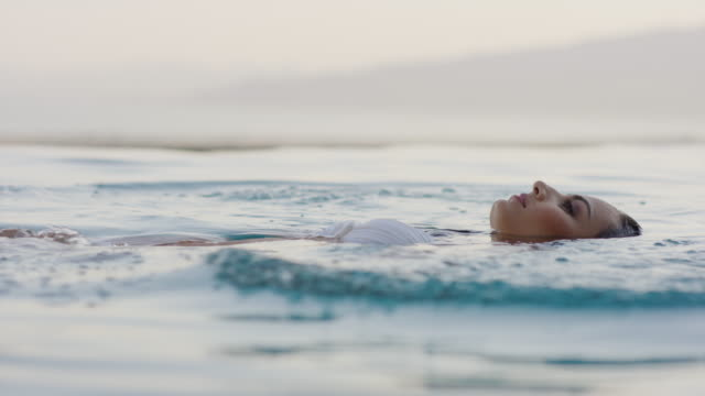 medium slow motion shot of woman floating in infinity pool / cedar hills, utah, united states - galleggiare sull'acqua video stock e b–roll