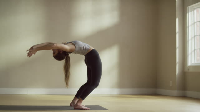 Medium slow motion shot of woman in upward bow pose / Provo, Utah, United States