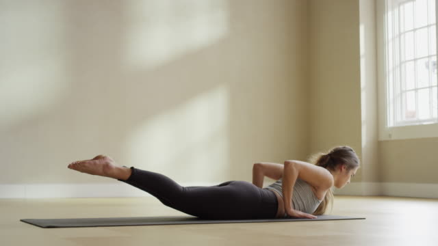 Medium slow motion shot of woman laying on mat performing yoga / Provo, Utah, United States