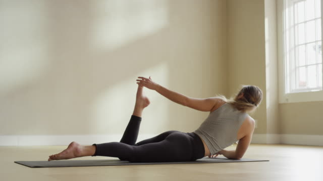 Medium slow motion shot of woman laying on mat stretching leg / Provo, Utah, United States