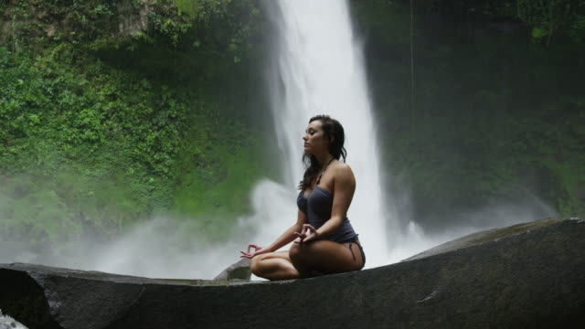 Medium slow motion shot of woman meditating near waterfall in rain forest / Arenal, La Fortuna, Costa Rica