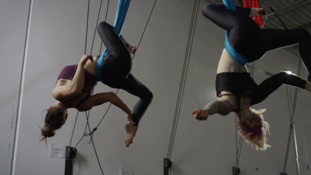medium slow motion shot of women practicing on aerial silks / midvale, utah, united states - mirror stock videos & royalty-free footage