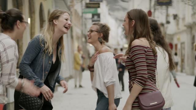 vídeos de stock, filmes e b-roll de medium slow motion shot of women talking and laughing in city / salzburg, austria - jaqueta jeans