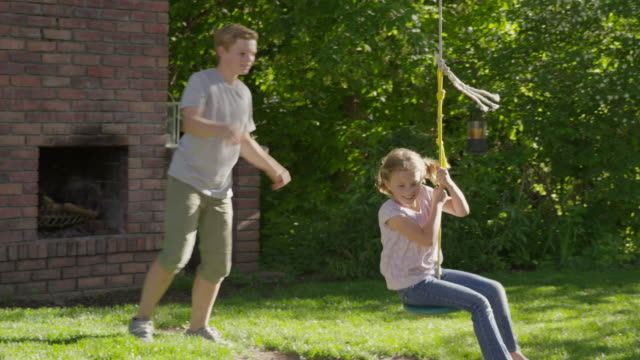 medium slow motion tracking shot of boy pushing girl on rope swing / springville, utah, united states - springville utah stock-videos und b-roll-filmmaterial