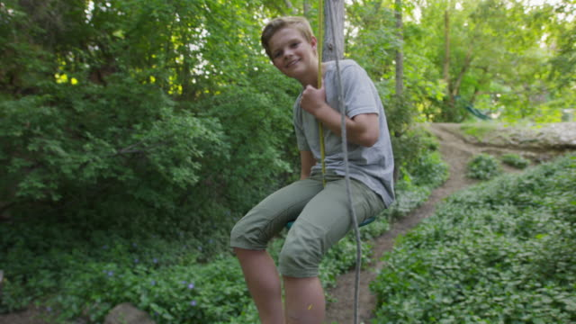 medium slow motion tracking shot of boy sitting on rope swing / springville, utah, united states - springville utah stock videos & royalty-free footage