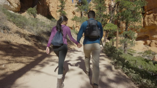 Medium slow motion tracking shot of couple hiking in desert / Bryce Canyon National Park, Utah, United States