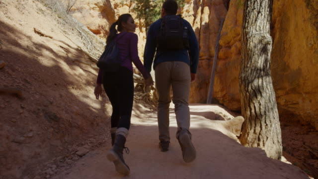 medium slow motion tracking shot of couple hiking in desert / bryce canyon national park, utah, united states - bryce canyon stock videos and b-roll footage