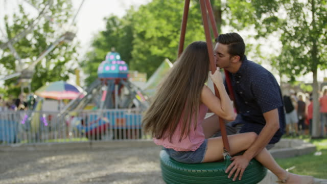 medium slow motion tracking shot of couple kissing on tire swing / pleasant grove, utah, united states - tyre swing stock videos & royalty-free footage