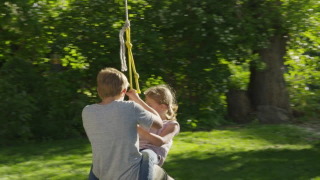 medium slow motion tracking shot of girl on lap of boy on rope swing / springville, utah, united states - springville utah stock-videos und b-roll-filmmaterial