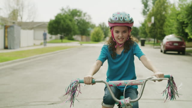 medium slow motion tracking shot of girl riding bicycle in street / provo, utah, united states - åka bildbanksvideor och videomaterial från bakom kulisserna