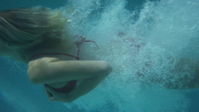 medium slow motion tracking shot of woman diving into pool / cedar hills, utah, united states - solo ragazze video stock e b–roll