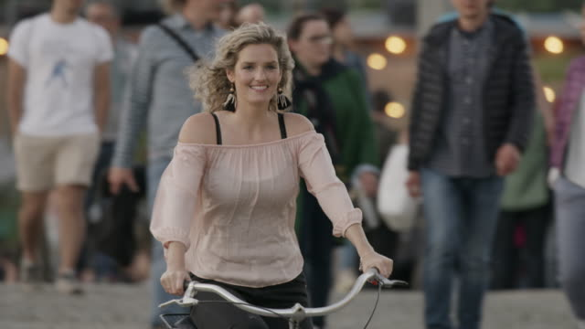 Medium slow motion tracking shot of woman riding bicycle / Berlin, Germany