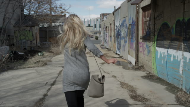 Medium slow motion tracking shot of woman running away in alley / Salt Lake City, Utah, United States