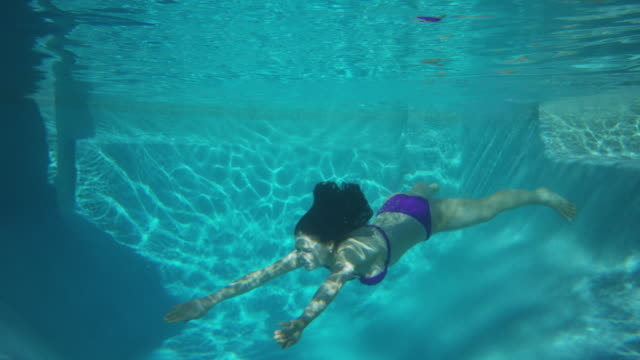Medium slow motion tracking shot of woman swimming underwater / Cedar Hills, Utah, United States