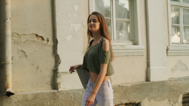 medium slow motion tracking shot of woman walking near building / plovdiv, bulgaria - shirt stock videos & royalty-free footage