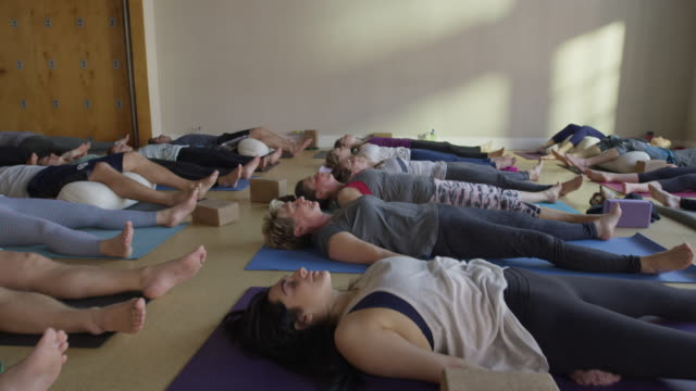 medium slow motion zoom out shot of yoga students in corpse pose / provo, utah, united states - nackenrolle kopfkissen stock-videos und b-roll-filmmaterial