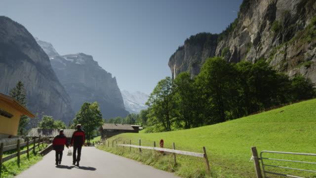 vídeos de stock e filmes b-roll de medium snot of road leading to remote town / lauterbrunnan, switzerland - vedação