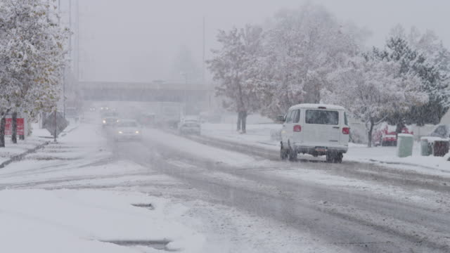 Medium snot of snow falling on cars driving on urban road / Orem, Utah, United States,