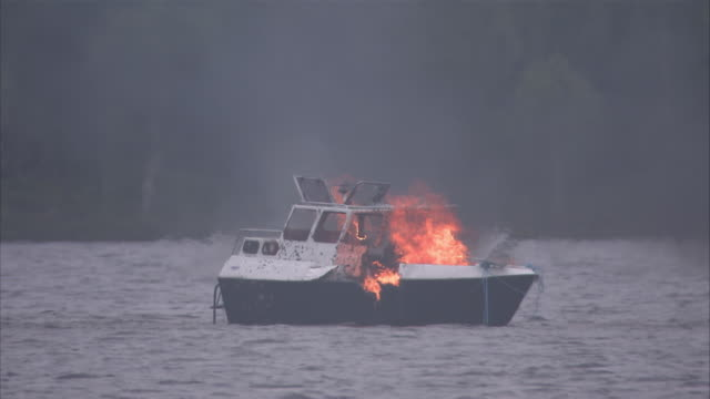 Medium static - A boat explodes in a ball of fire as it floats on a lake.
