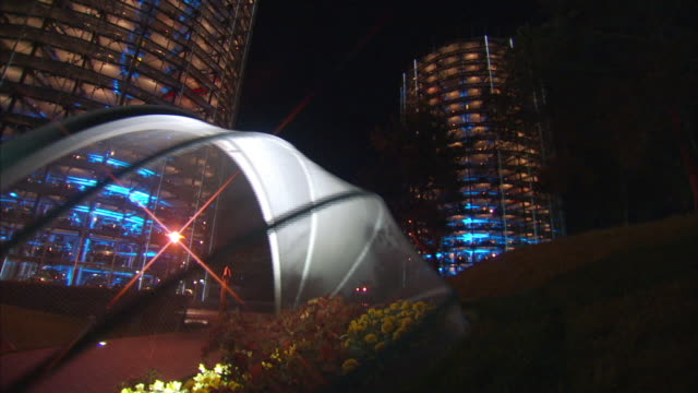 medium static - a bubble greenhouse protects flowers adjacent to the volkswagen car towers at the autostadt. / wolfsburg, germany - gewächshäuser stock-videos und b-roll-filmmaterial