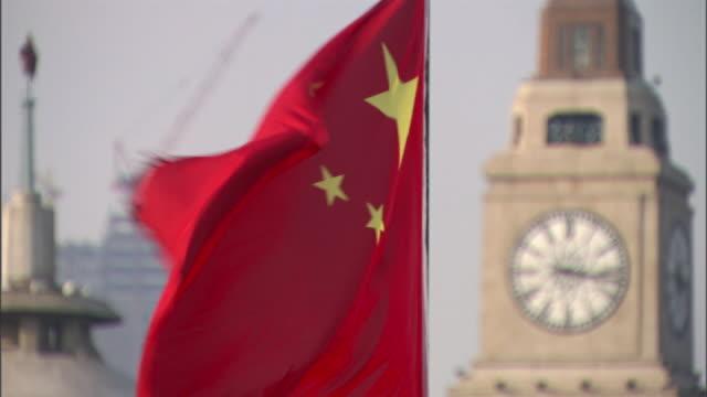 Medium static - A Chinese flag flutters near a clock tower. / Shanghai, China