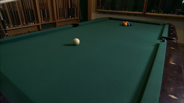 medium static - a pool player uses a cue stick to hit the cue ball into racked billiard balls /  wisconsin, united states - pool cue sport stock videos & royalty-free footage