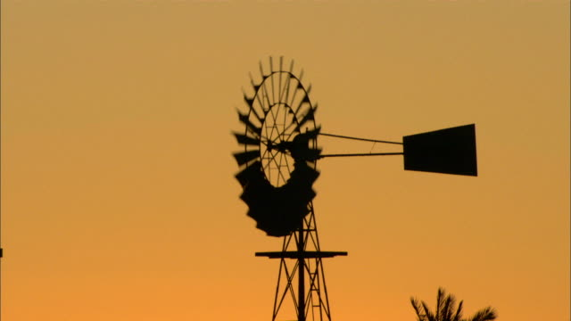 medium static - a silhouetted windmill spins at sunset / simpson desert, australia - mill stock videos & royalty-free footage