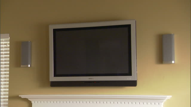 medium static , a television hangs on a living room wall above a fireplace mantel. /  - television static stock videos & royalty-free footage