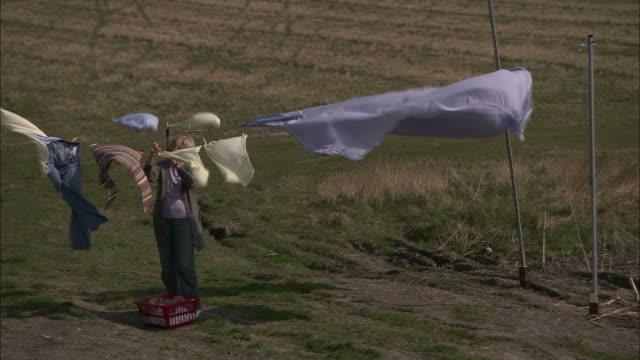 stockvideo's en b-roll-footage met medium static - a woman hangs laundry on a clothesline as a strong wind billows the clothes around her - wasmand