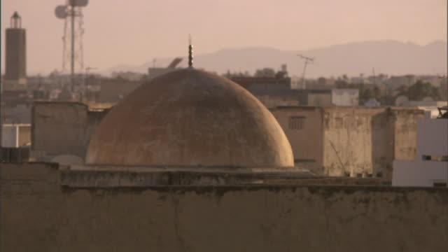 Medium static - An antenna leans behind a dome near mountains in Libya. / Libya