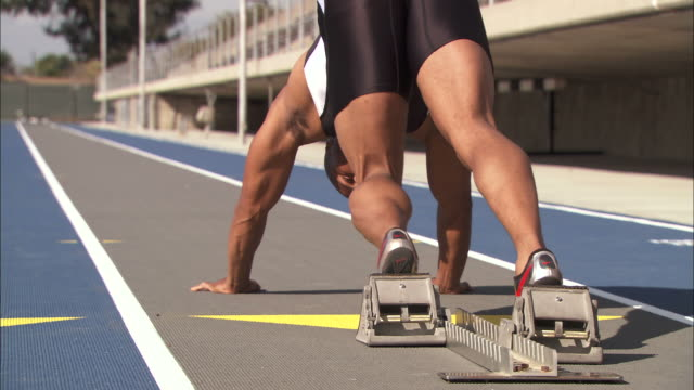 Medium static - An athlete uses starting blocks as he begins a sprint