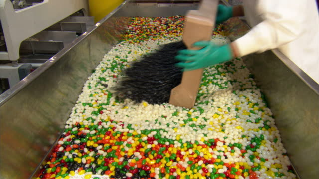 medium static - factory workers mix a variety of jellybeans in a bin /  utah, united states - sweet food stock videos & royalty-free footage