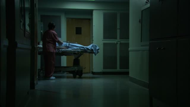 medium static - medical staff wheels a patient along a dim hospital corridor - stretcher stock videos & royalty-free footage