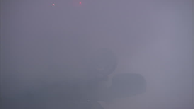 medium static - smoke drifts past a patrol car as a police officer jumps in the car, and backs the car out - emergency siren stock videos and b-roll footage
