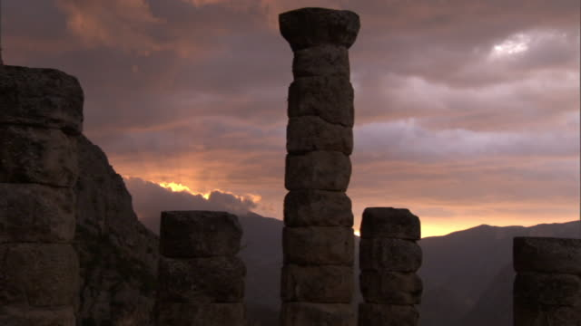Medium static - Stone columns tower over the Delphi archeological site at sunset. / Delphi, Greece