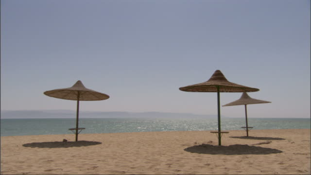 Medium, static - Umbrellas provide pools of shade on a wide, flat beach / Egypt