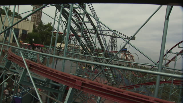 medium static - young adults scream as they ride a roller coaster. / barcelona, spain - amusement park ride stock videos and b-roll footage