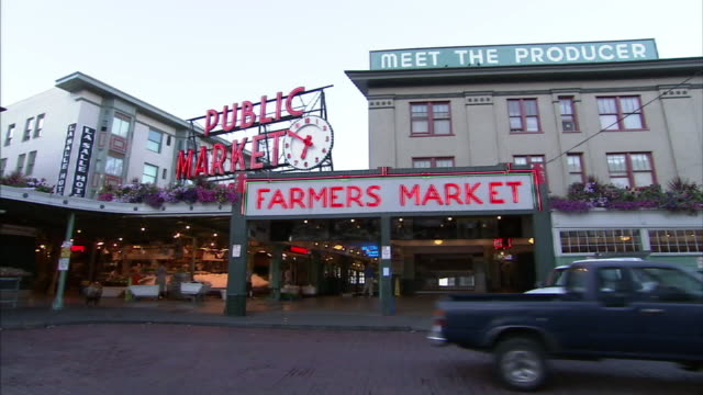 medium static-light traffic passes a farmer's market in seattle's public market center. / seattle, washington, usa - seattle stock-videos und b-roll-filmmaterial