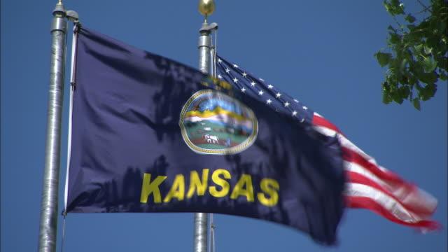 Medium static-The Kansas state flag waves next to the flag of the United States of America. / Kansas, USA