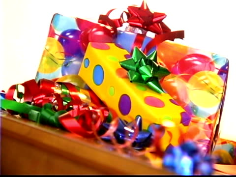 vidéos et rushes de medium still life of a pile of colorfully wrapped gifts rack focusing to a blurred background. - noeud à boucle