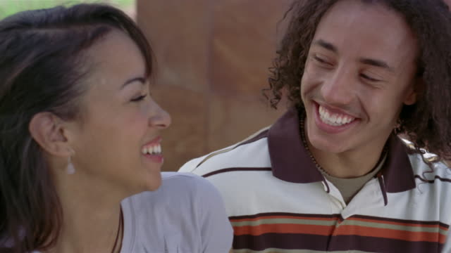 vidéos et rushes de medium teenage couple smiling at one another and laughing - couple d'adolescents
