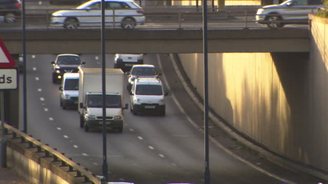 medium tilt tracking traffic as it descends under a bridge outer london uk - motorway junction stock videos & royalty-free footage