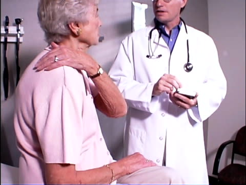 stockvideo's en b-roll-footage met medium tilt up of elderly woman showing doctor about shoulder pain during office visit. the doctor is using a palmtop for patient file notes. - driekwartlengte